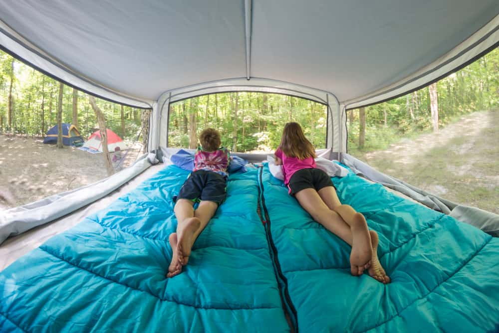 Two children look out over a campsite from their sleeping bags in a pop up camper.