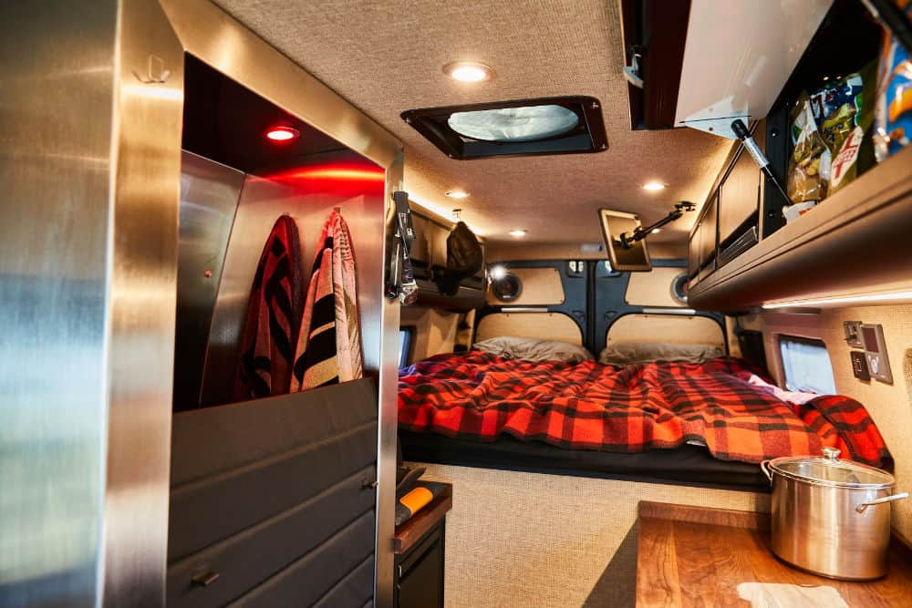Bed, closet and storage space inside a 4x4 Sprinter van camper