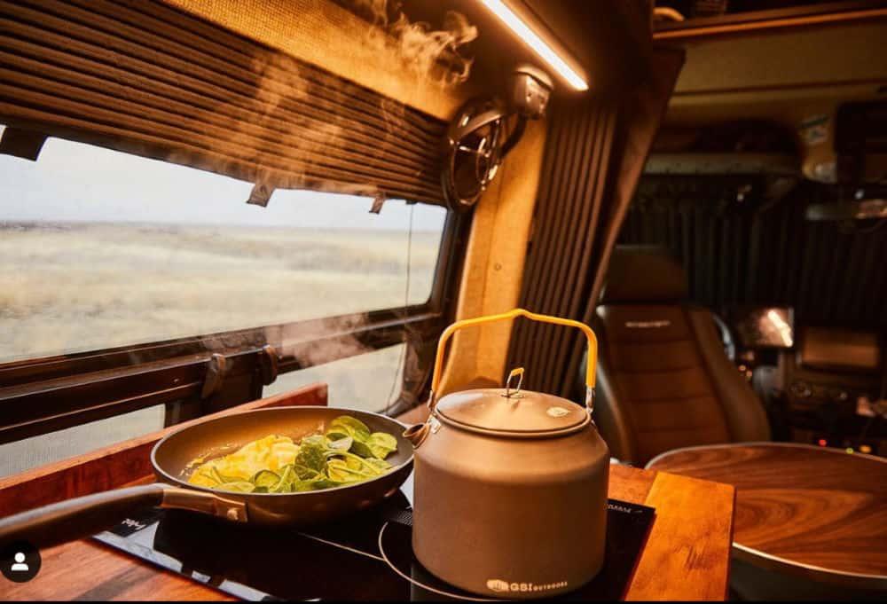 Pan cooking breakfast near kettle inside a 4x4 Sprinter van camper