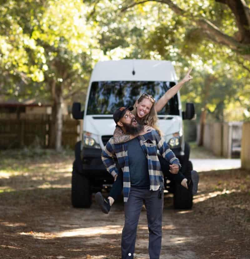 Kate and Levi in front of a white 4x4 Sprinter van camper