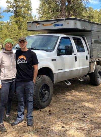 Joe and Kait Russo standing in front of their pop up truck camper