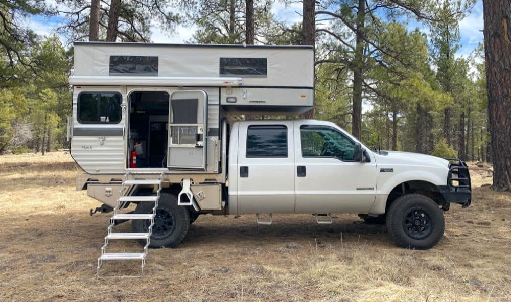 Four Wheel pop up camper with the top popped and ladder going inside