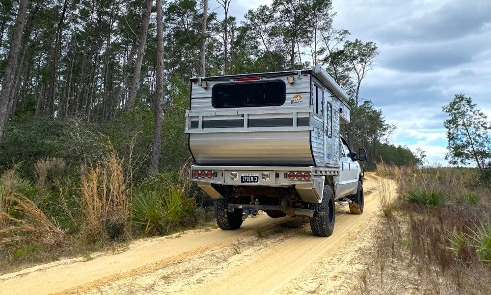 Four Wheel truck camper driving down the road