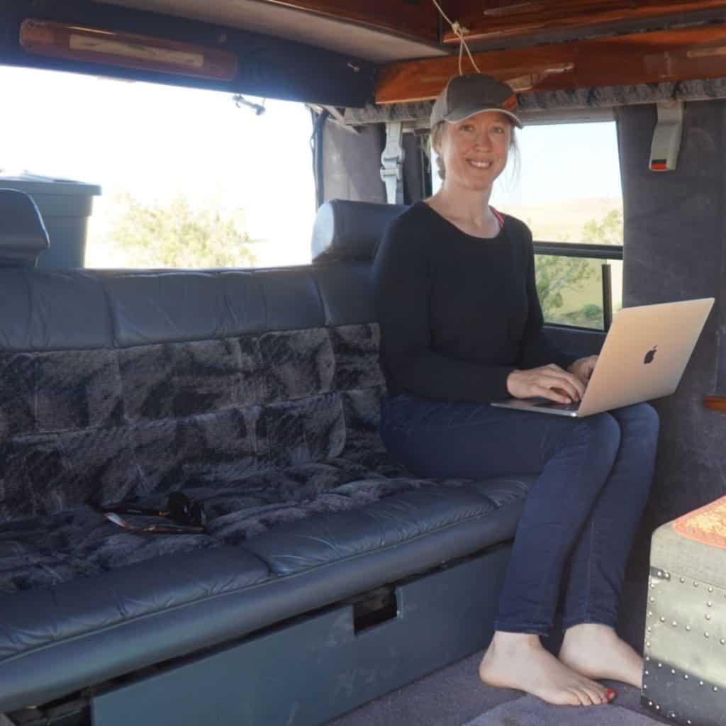 Woman working on a laptop computer using van life internet inside an Astro van