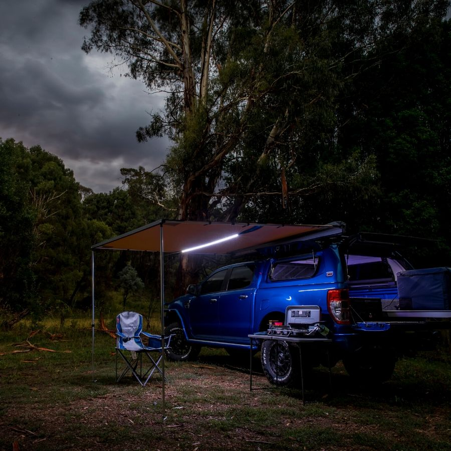 ARB awning with LED light set up with dark storm clouds in background.