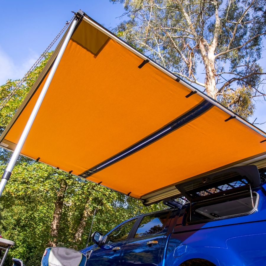 Orange ARB awning pictured from underneath, attached to a vehicle. The LED light strip is visible.