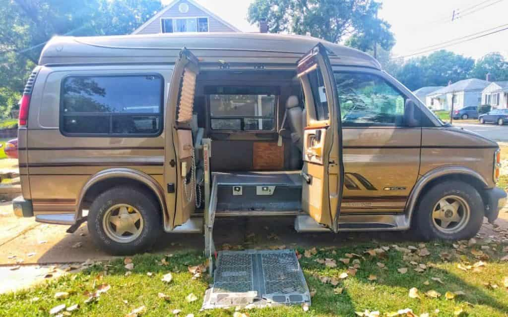 Brown Dodge conversion van with side doors open to see van interior, one of the best vans to live for affordability