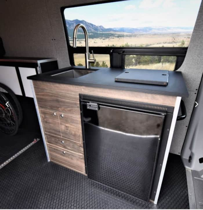 Sprinter van kit components include this kitchen with countertop, sink, fridge and cupboards.