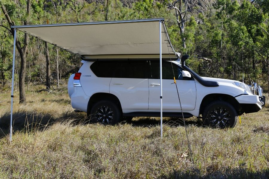The Dobinson's van awning set up on an SUV in tall grass.