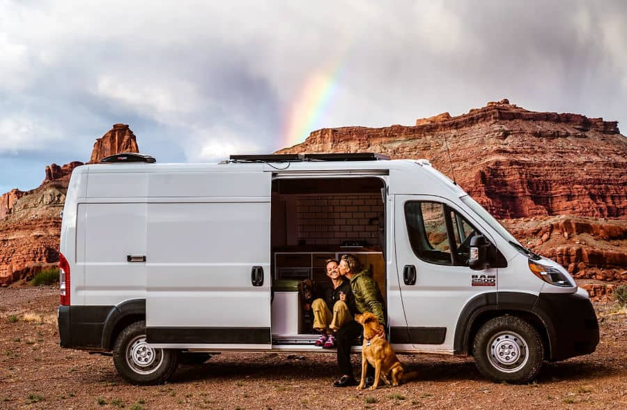 A couple sitting on the side of a Dodge Promaster camper, one of the best wide vans to live in