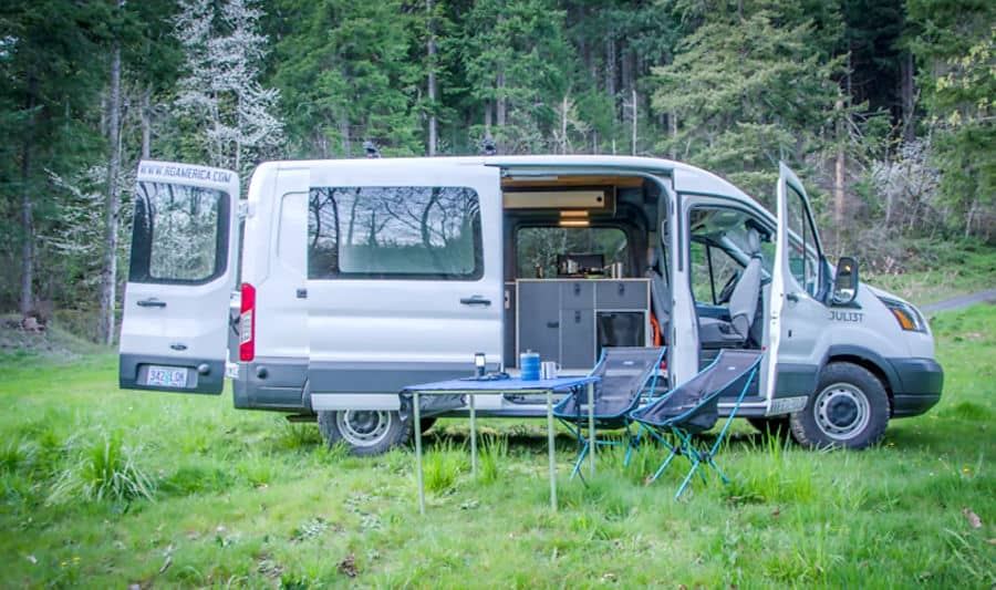 Ford Transit campervan with side doors open with a kitchen inside, considered one of the best vans for van life