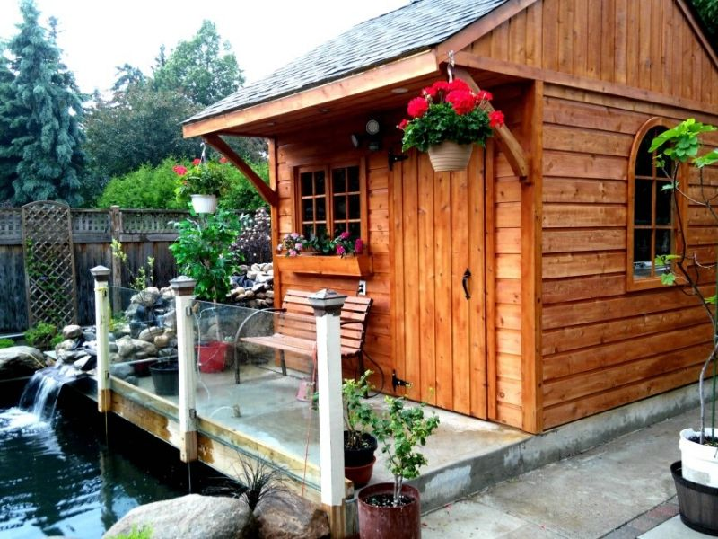 Glen Echo Cabin tiny house kit under $5,000 built over a pond with cedar planking and cement slab/porch.