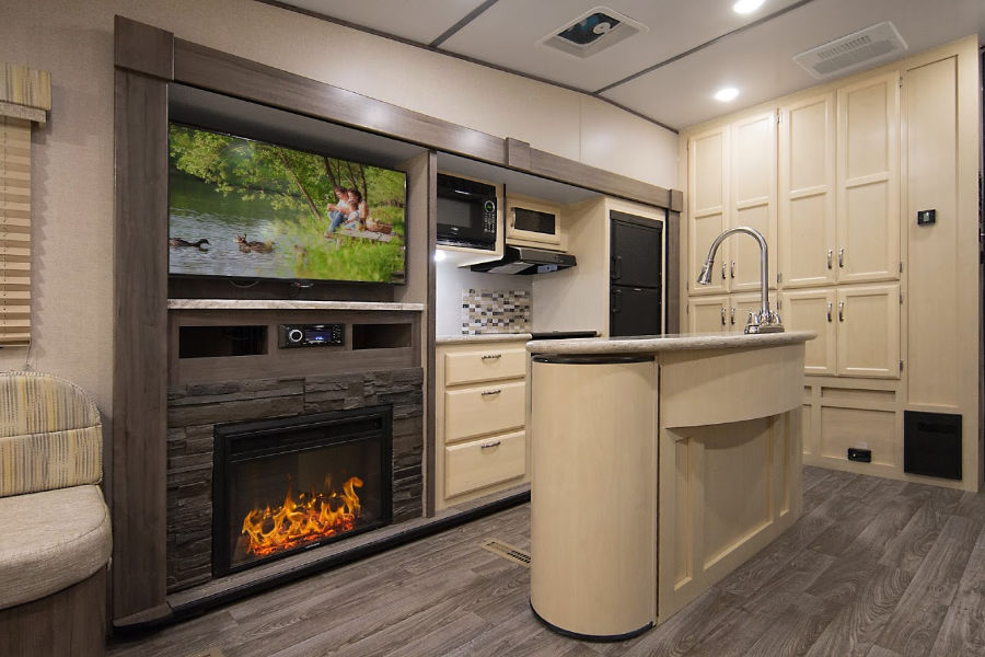 The spacious interior of the Winnebago Plus small 5th wheel trailer includes a large kitchen for entertaining