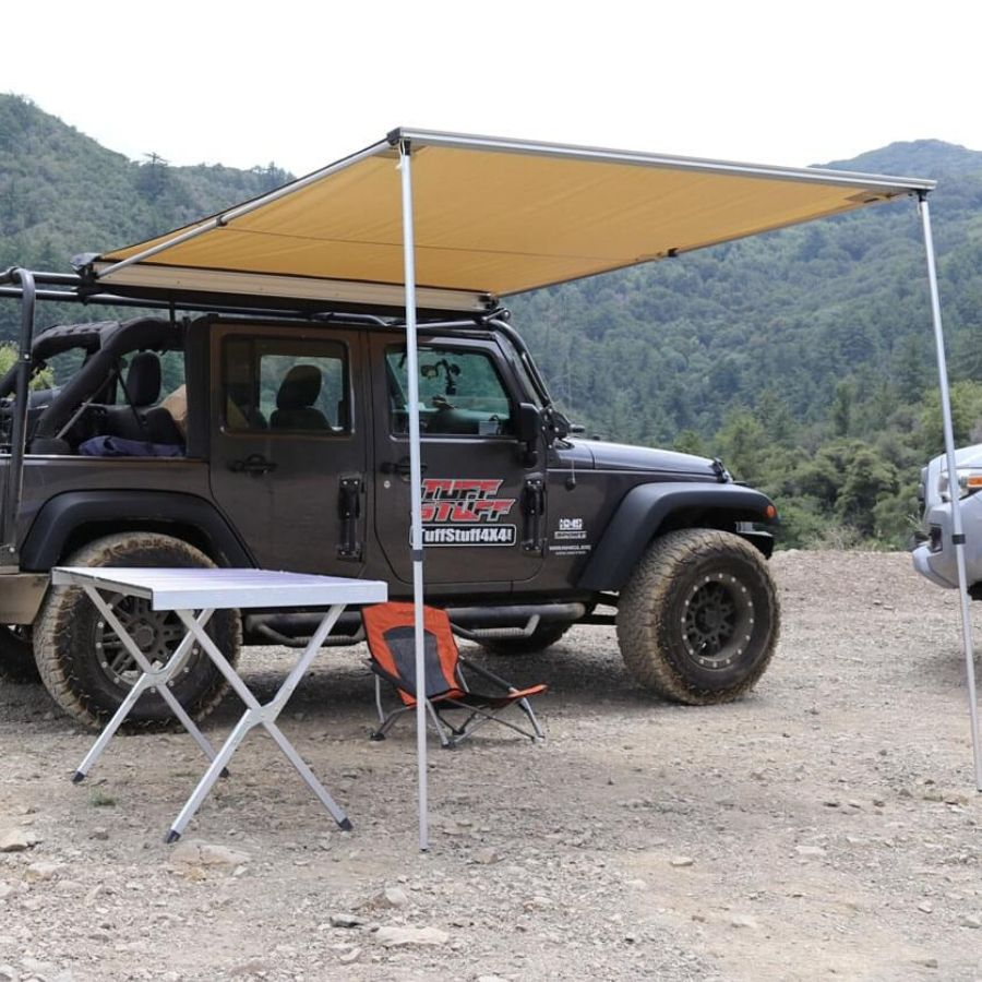 TuffStuff awning attached to a Jeep set up on a gravel campsite.