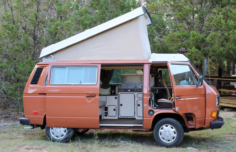 Orange VW Westfalia camper with the pop topped and side door open