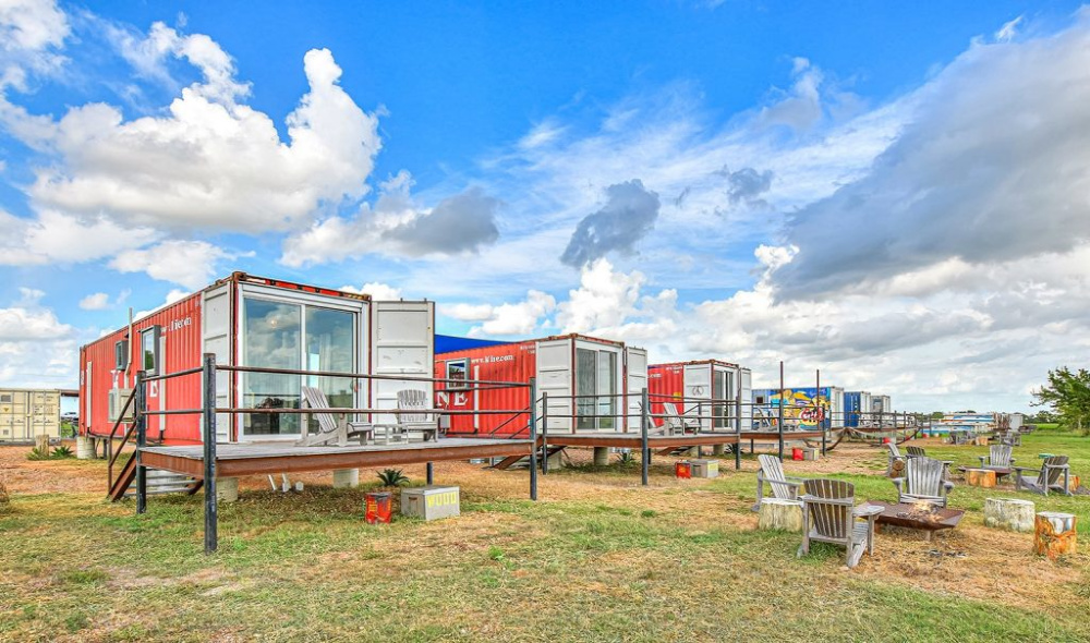 Flophouze hotel, with multiple container houses with decks lined up in a row, ready for guests.
