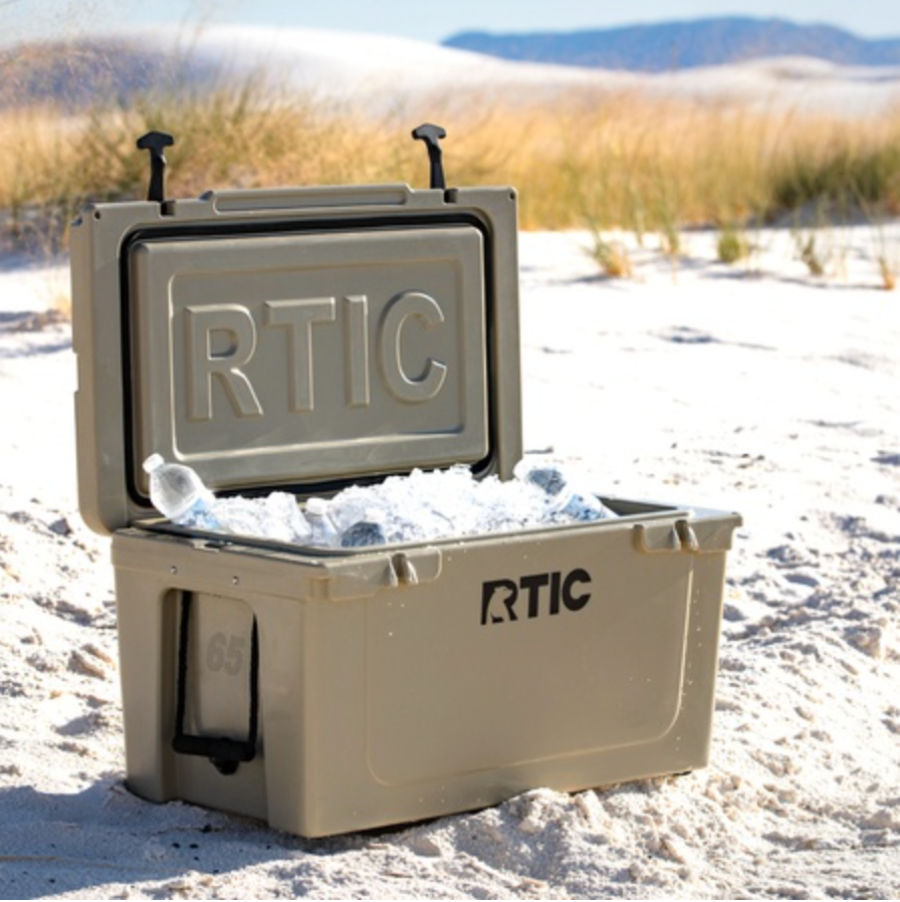 The RTIC cooler is one of the best coolers for van life, shown open in a desert with ice and water bottles
