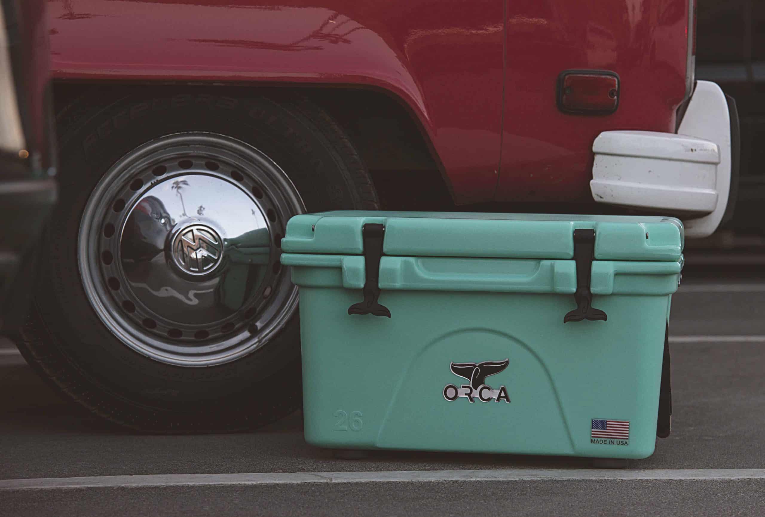 green van life cooler next to a red van