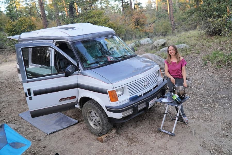 Woman cooking outside a camper van with a Jet Boil stove, one of the best van life essentials