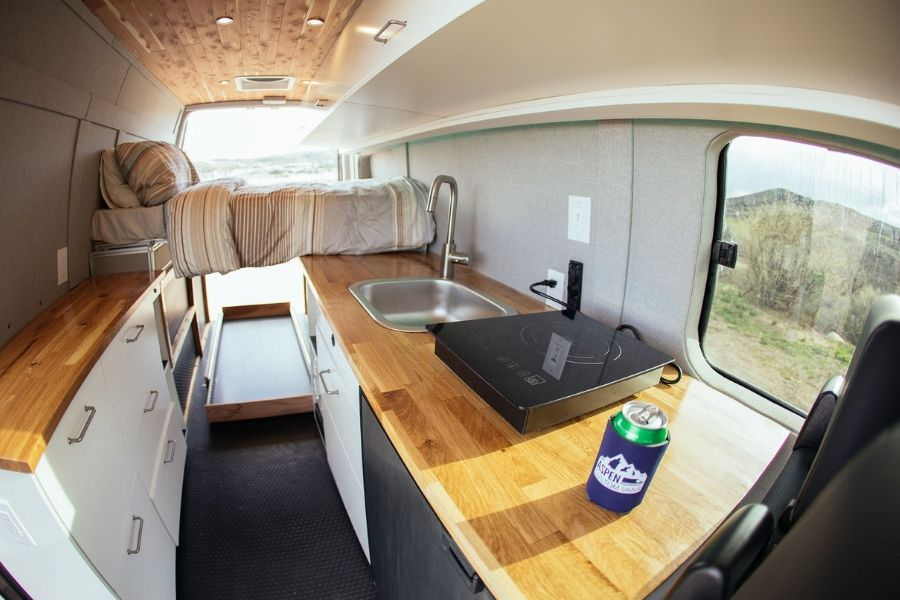 Aspen Custom Vans converted this van with wooden counter tops and lofted bed