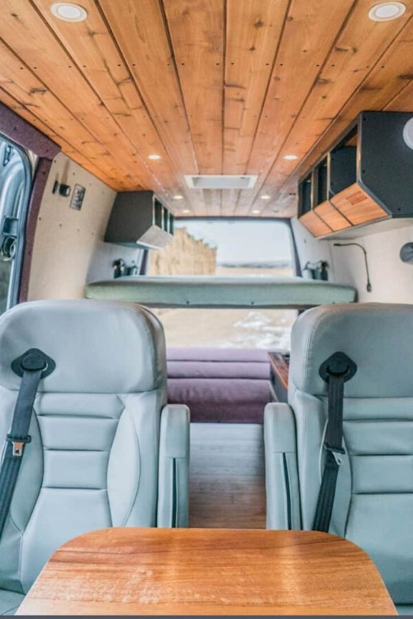 Van converted by Beartooth Vanworks camper van conversion company has a super sleek, modern look with light blue chairs and bed and wooden touches throughout.