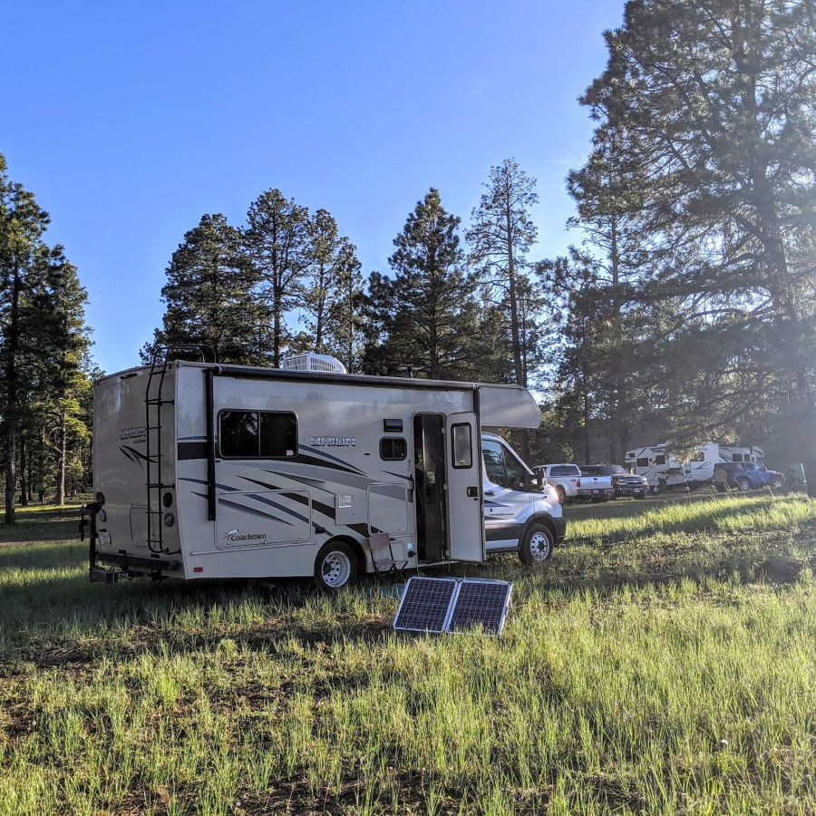 Class C RV parked in the grass with solar panels