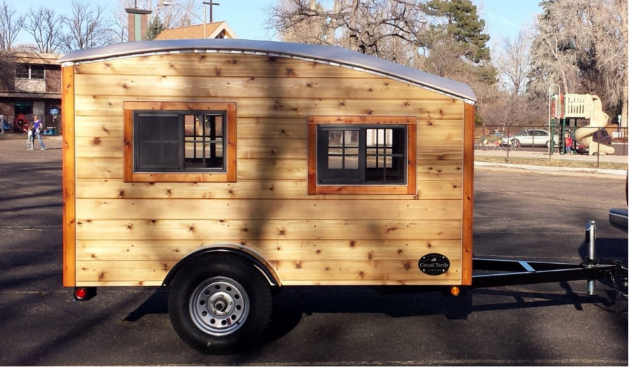 The Hatchling small travel trailer with wood paneling and a single axle
