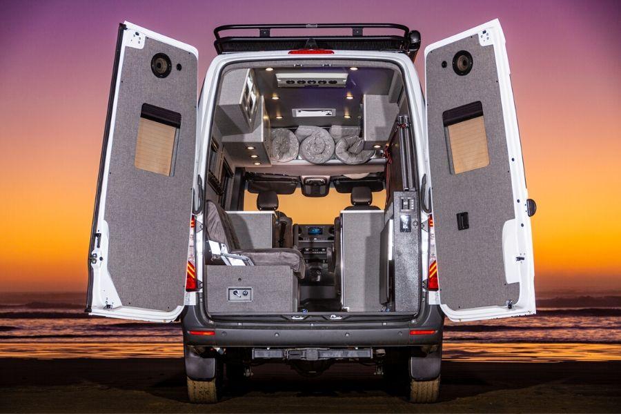 View from rear doors of El Kapitan van conversion shows all grey, neatly organized van interior.