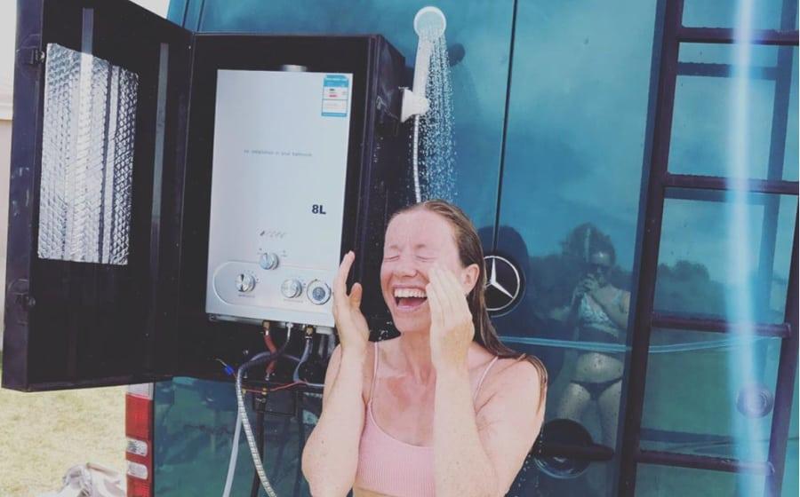 woman taking van life shower outside sprinter van