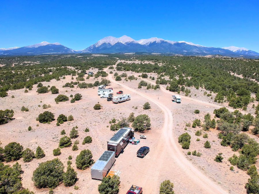 Group of RVs parked next to each other in the desert with mountains in the distance