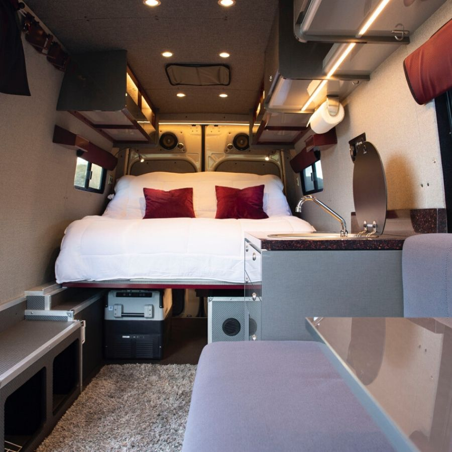 Sync Vans conversion with fluffy white bed and comfy dining booth