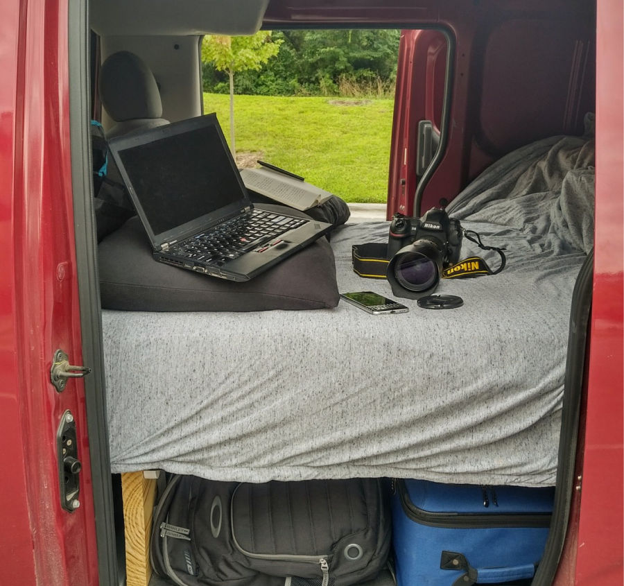 A computer and camera set up on the bed inside an nv200 camper