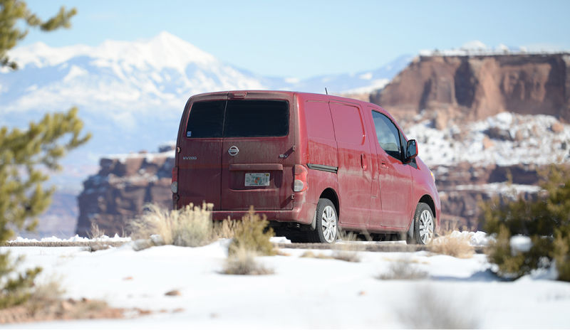 NV200 camper parked on the edge of a snowy desert cliff
