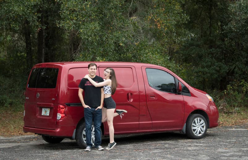 couple standing by red NV200 camper