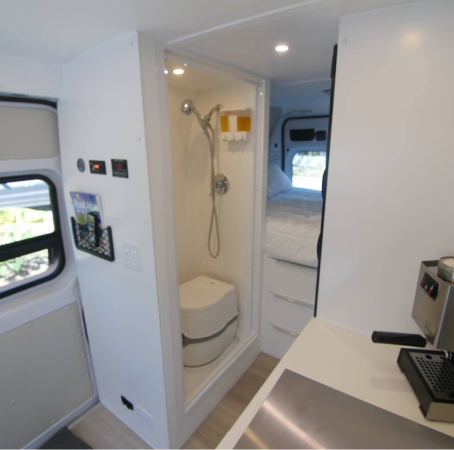 Indoor van life shower inside a Dodge Promaster with a cassette toilet