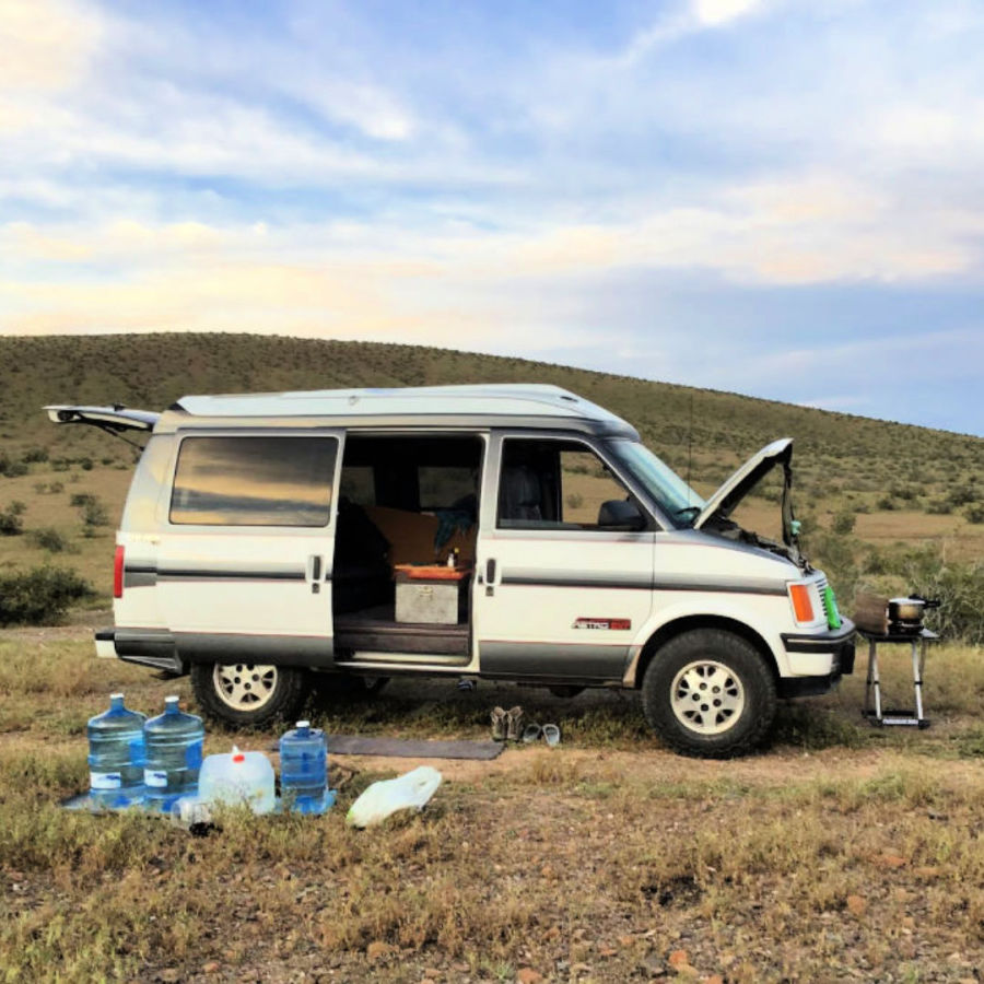 Campervan boondocking with four water jugs out front