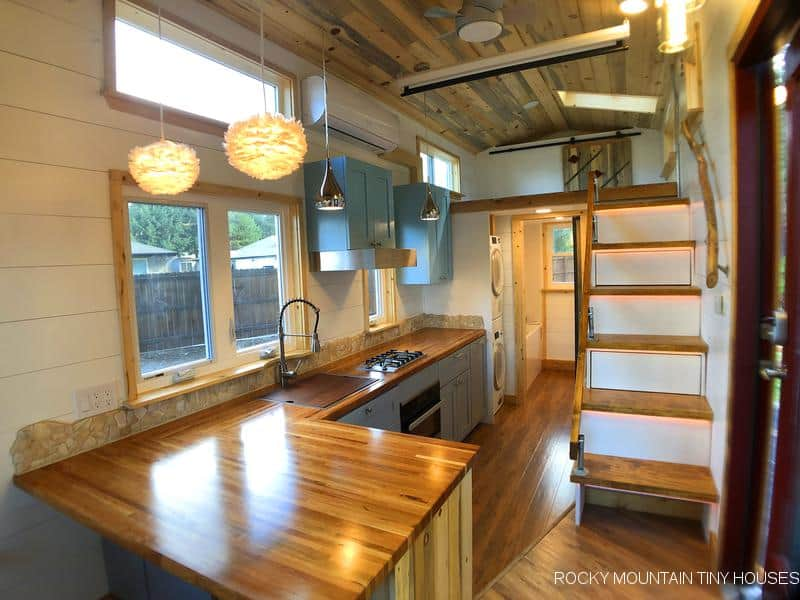Interior of the Bradford off grid tiny house on wheels with large counter space and stairway
