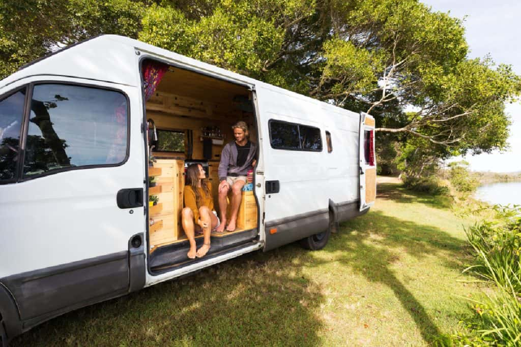 Couple sitting inside a DIY campervan living van life