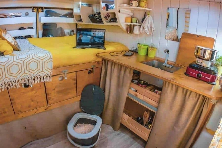 Interior of campervan with small portable toilet on the floor