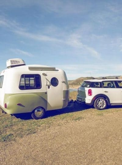 HC! Happier Camper Micro camper hitched to a car on the beach