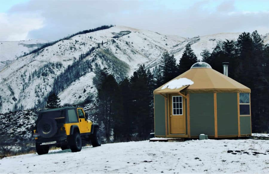 Green yurt off grid tiny home parked in the snowy mountains