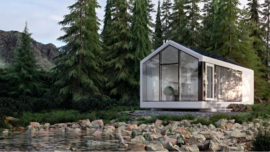 M One Off-Grid Tiny Home parked in the forest by a stream