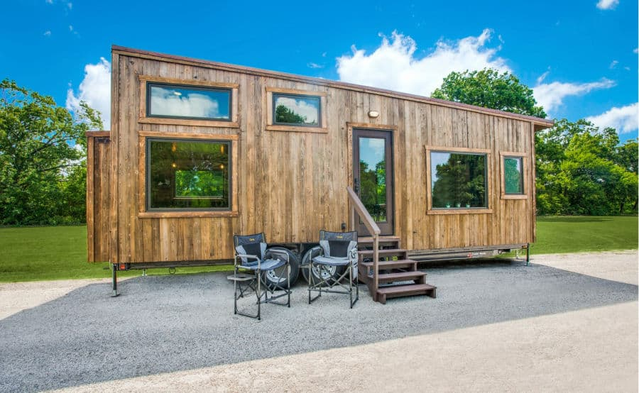 Thoreau tiny house on wheels with two camping chairs out front