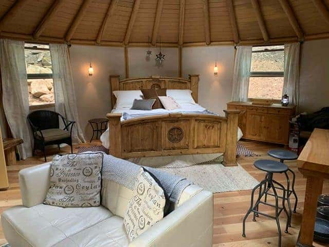 Interior of a yurt off grid tiny house with couch and bed