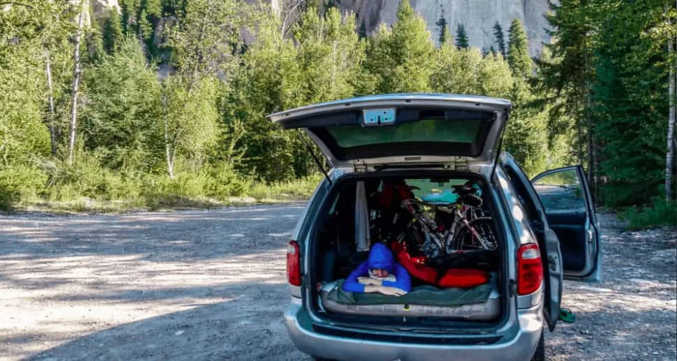 The Dodge Caravan with hatch open and woman lying in back makes a great affordable camper van