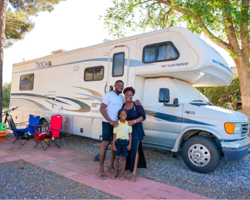 Family of three standing next to their Class C RV
