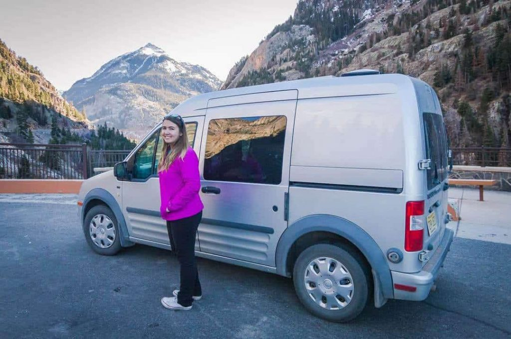 Woman standing next to a Ford Transit connect, an awesome affordable camper van
