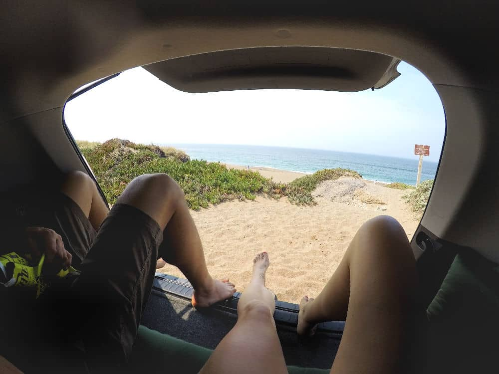 Two people sitting in the back of a Prius while living in a car