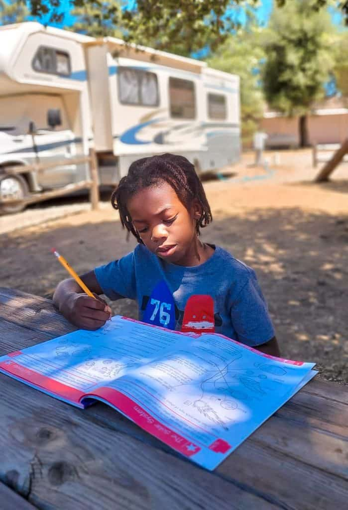RVing kid doing school work at a picnic table