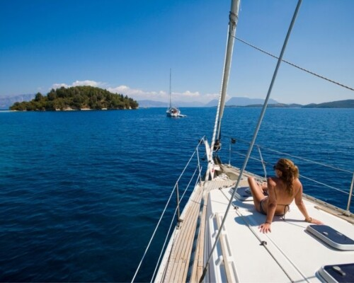 Woman lays on sailboat on the ocean with an island in the background